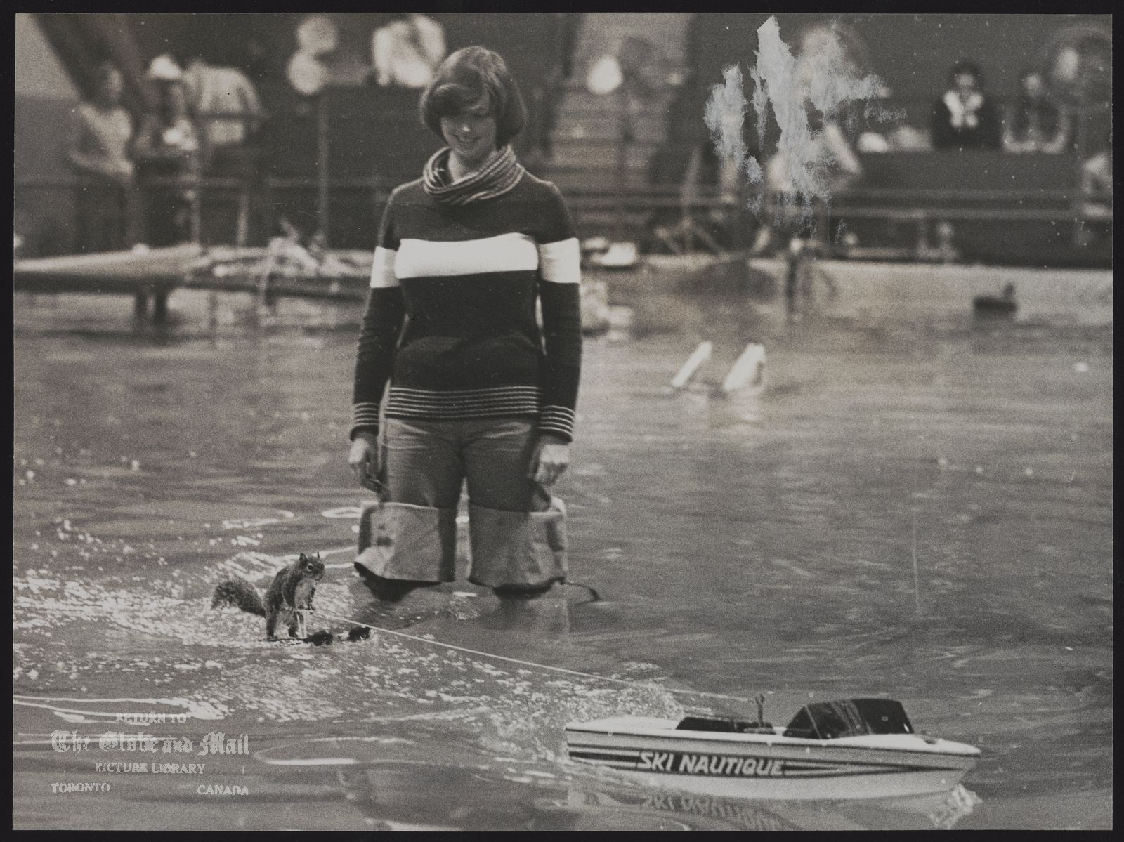 The notes transcribed from the back of this photograph are as follows: SQUIRRELS Lou Ann Best stands in the pool in hip waders as she watches Twiggy, the 3 year old Florida Grey squirrel water skis behind a radio controlled boat.