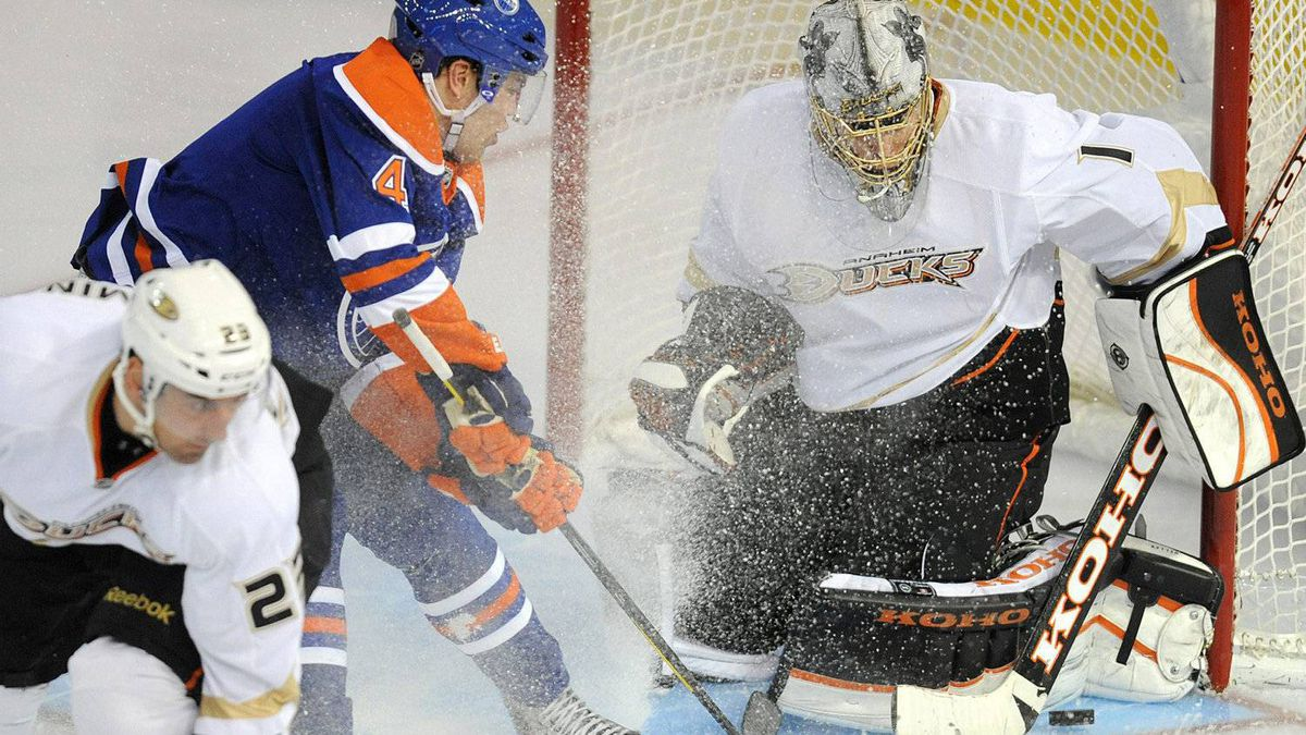 Edmonton Oilers' Taylor Hall, centre, shots at Anaheim Ducks goalie Jonas Hiller as Francois Beauchemin, left, defends during second period NHL hockey action in Edmonton on Friday, January 13, 2012. THE CANADIAN PRESS/John Ulan
