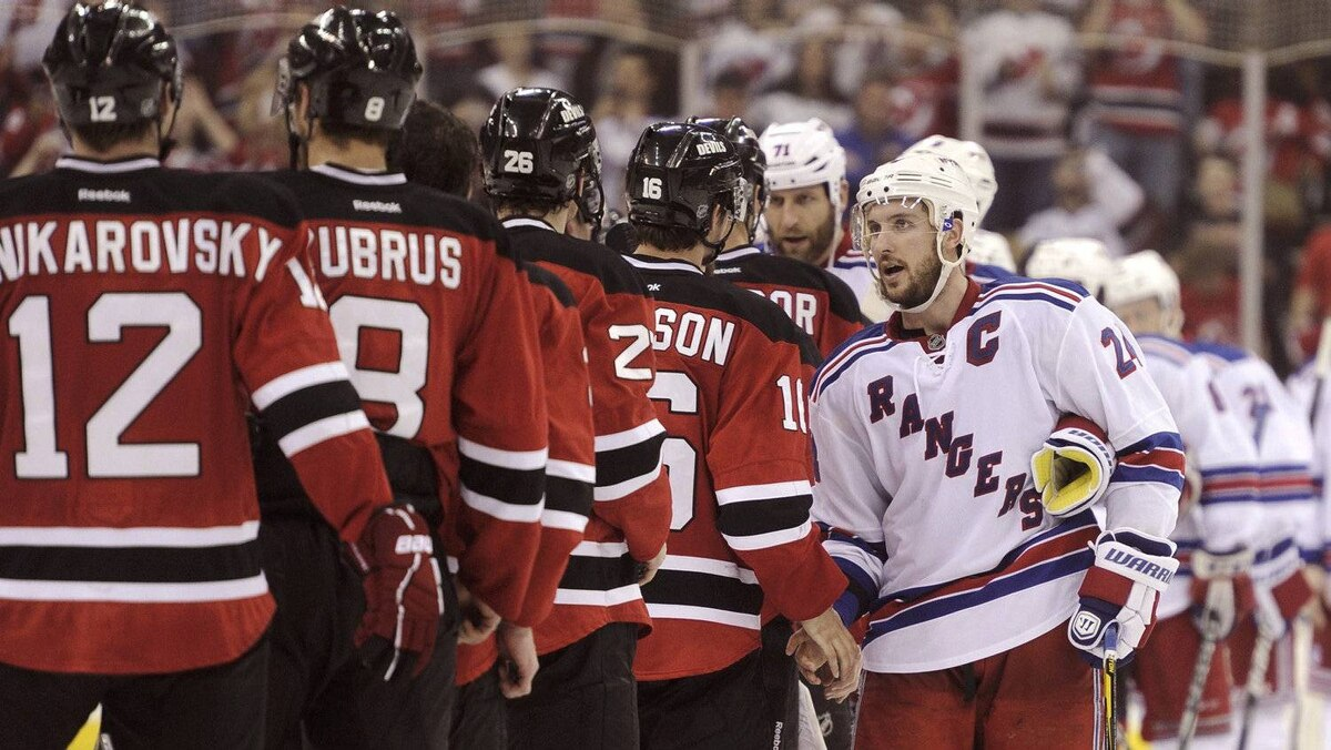 New York Rangers' Ryan Callahan (R) shakes hands with the New Jersey Devils after the Devils won Game 6 of their NHL Eastern Conference Final game to advance to the Stanley Cup Finals, in Newark, New Jersey, May 25, 2012.