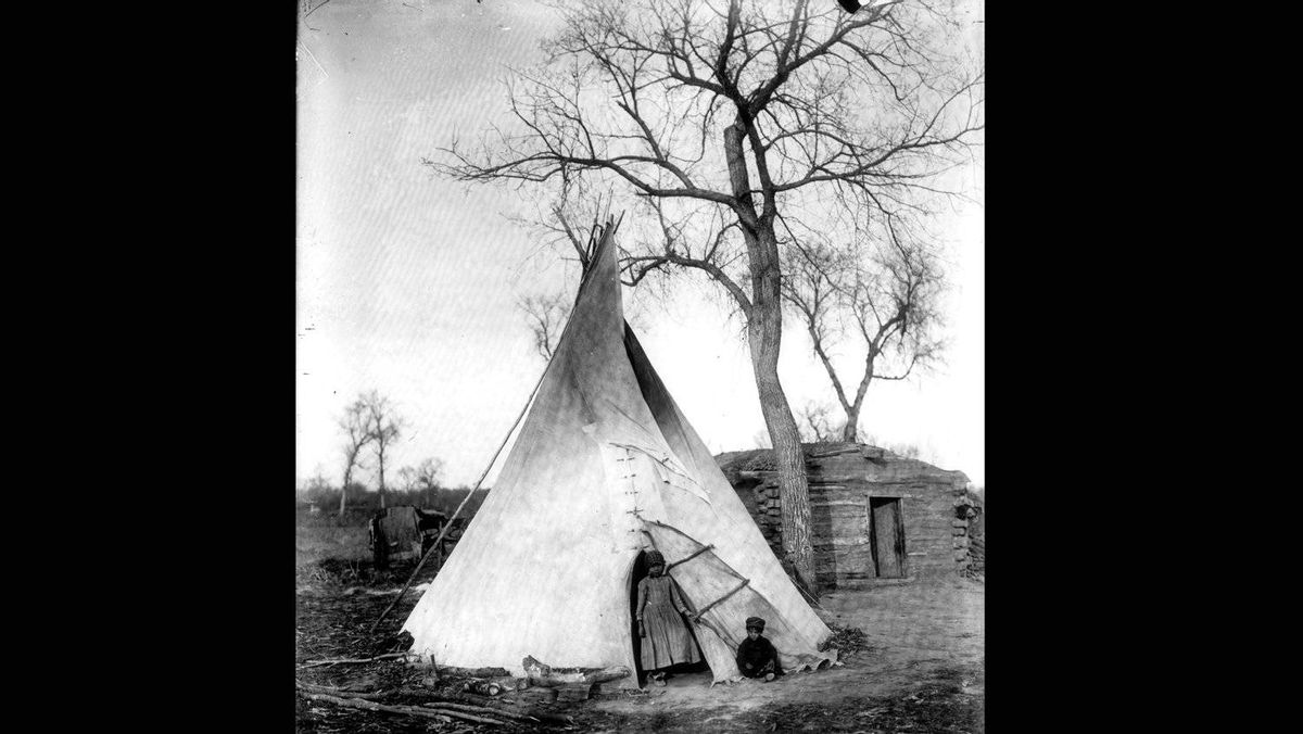 Young children pose in front of a teepee and log cabin in Portage La Prairie in 1904.