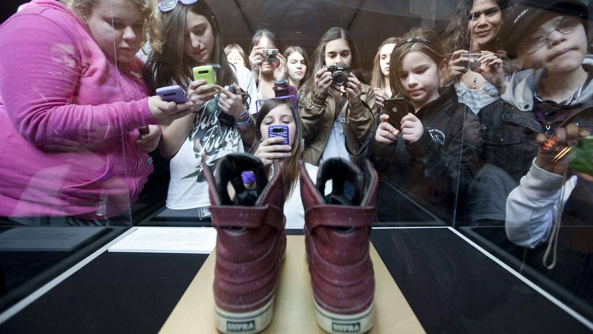 Fans crowd a pair of sneakers worn by Justin Bieber that are now encased in glass at the Bata Shoe Museum in Toronto.