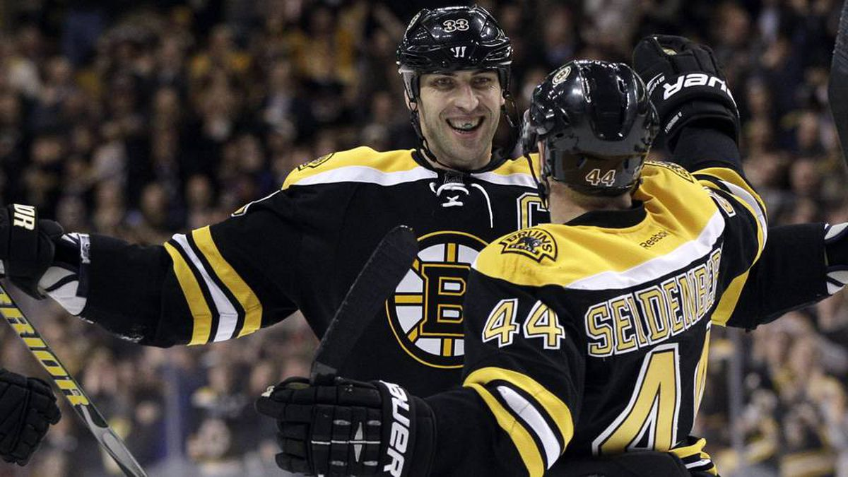 Boston Bruins defenseman Zdeno Chara celebrates with defenseman Dennis Seidenberg after Seidenberg scored against the Tampa Bay Lightning in the second period of an NHL hockey game in Boston, Tuesday, March 27, 2012.