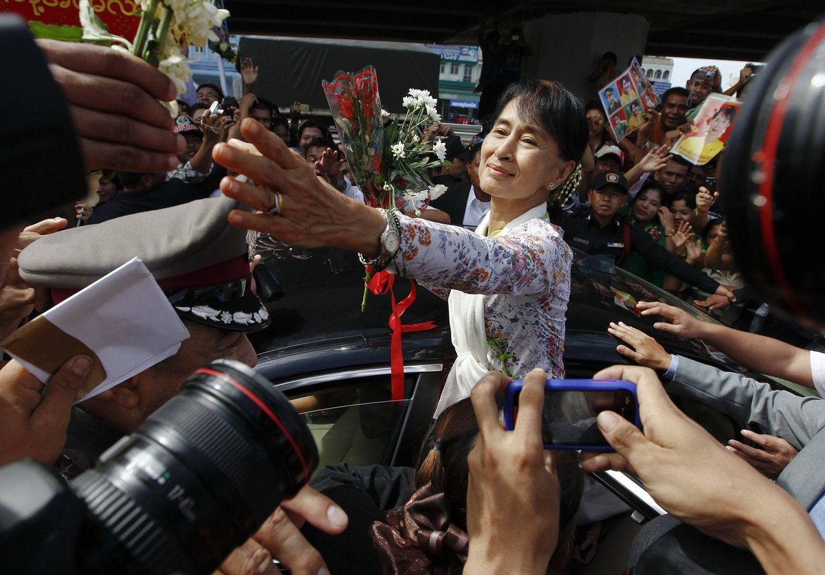 Myanmar's pro-democracy leader Aung San Suu Kyi receives flowers from migrant workers from Myanmar, as she visits them in Samut Sakhon province. Nobel Peace Prize winner Suu Kyi ventures outside Myanmar for the first time in 24 years on Tuesday in an unmistakable display of confidence in the liberalisation taking shape in her country after five decades of military rule.