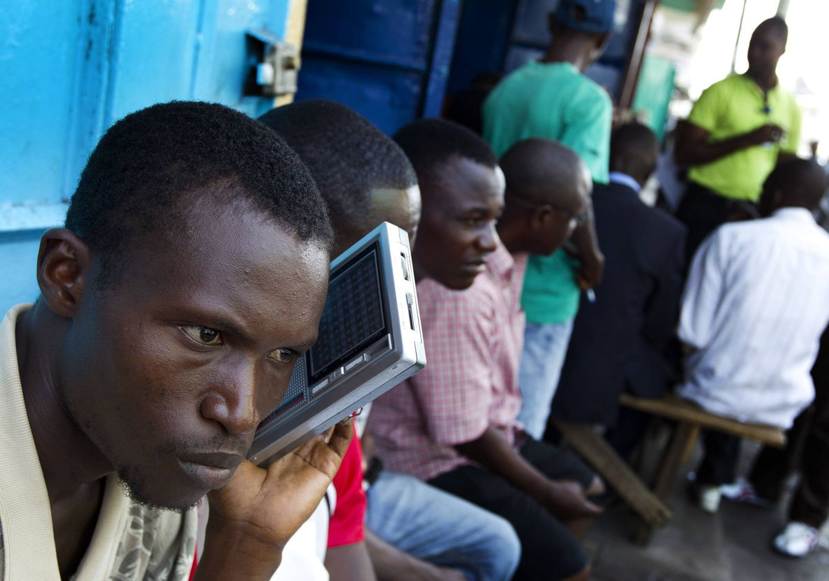 A amn listens to a portable radio in downtown Monrovia, Liberia as the verdict against former Liberian President Charles Taylor is read.