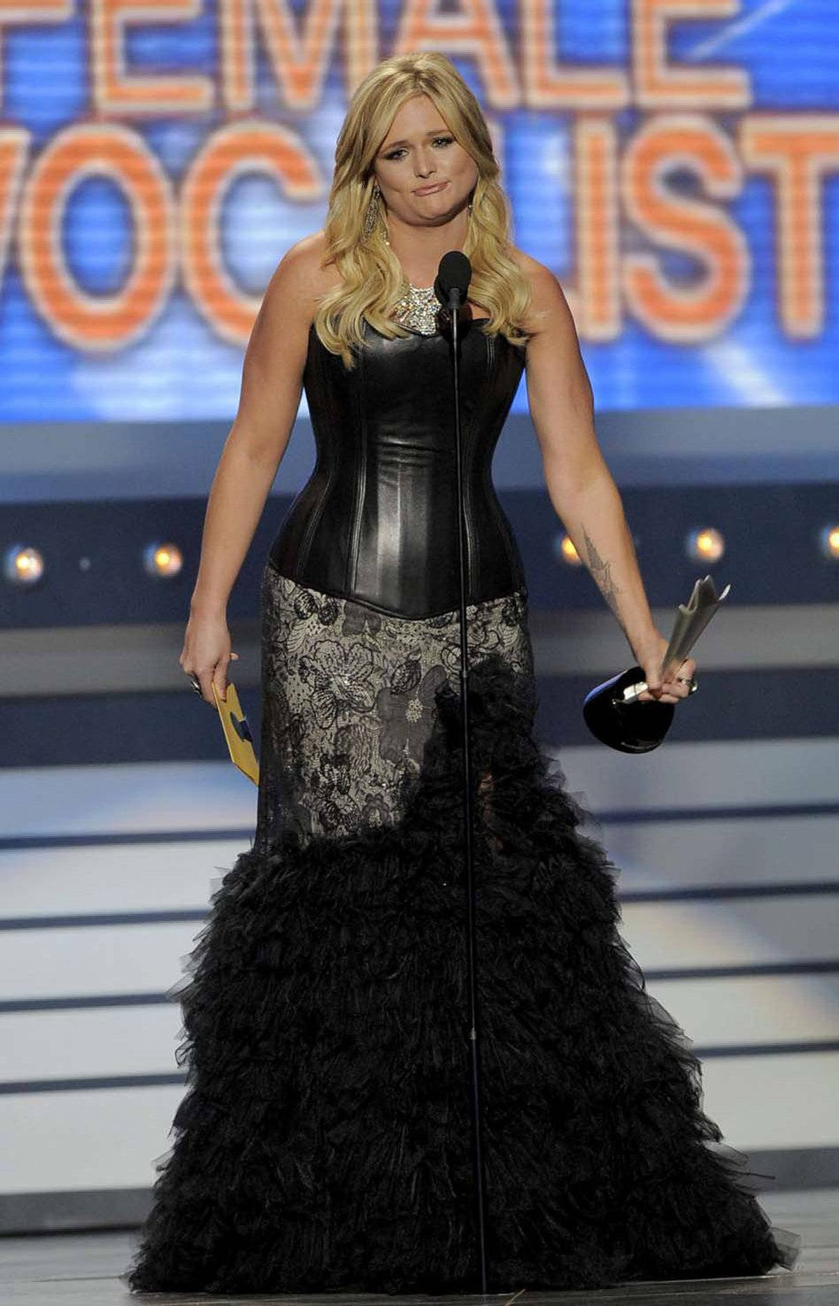 Miranda Lambert accepts one of her two awards at the Academy of Country Music Awards in an unfunny caption that serves only to set up the obvious joke in the next photo.
