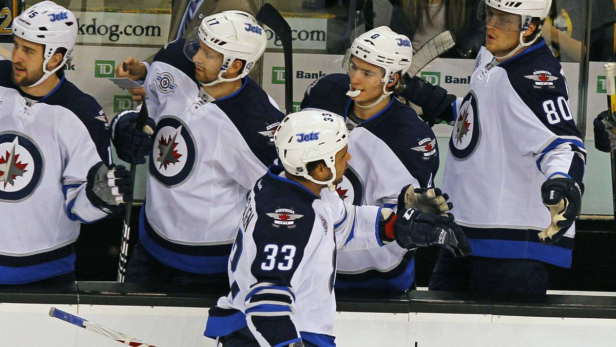 Winnipeg Jets defenseman Dustin Byfuglien (33) is congratulated by teammates after scoring against the Boston Bruins in first period action during their NHL hockey game in Boston, Massachusetts November, 26 2011.