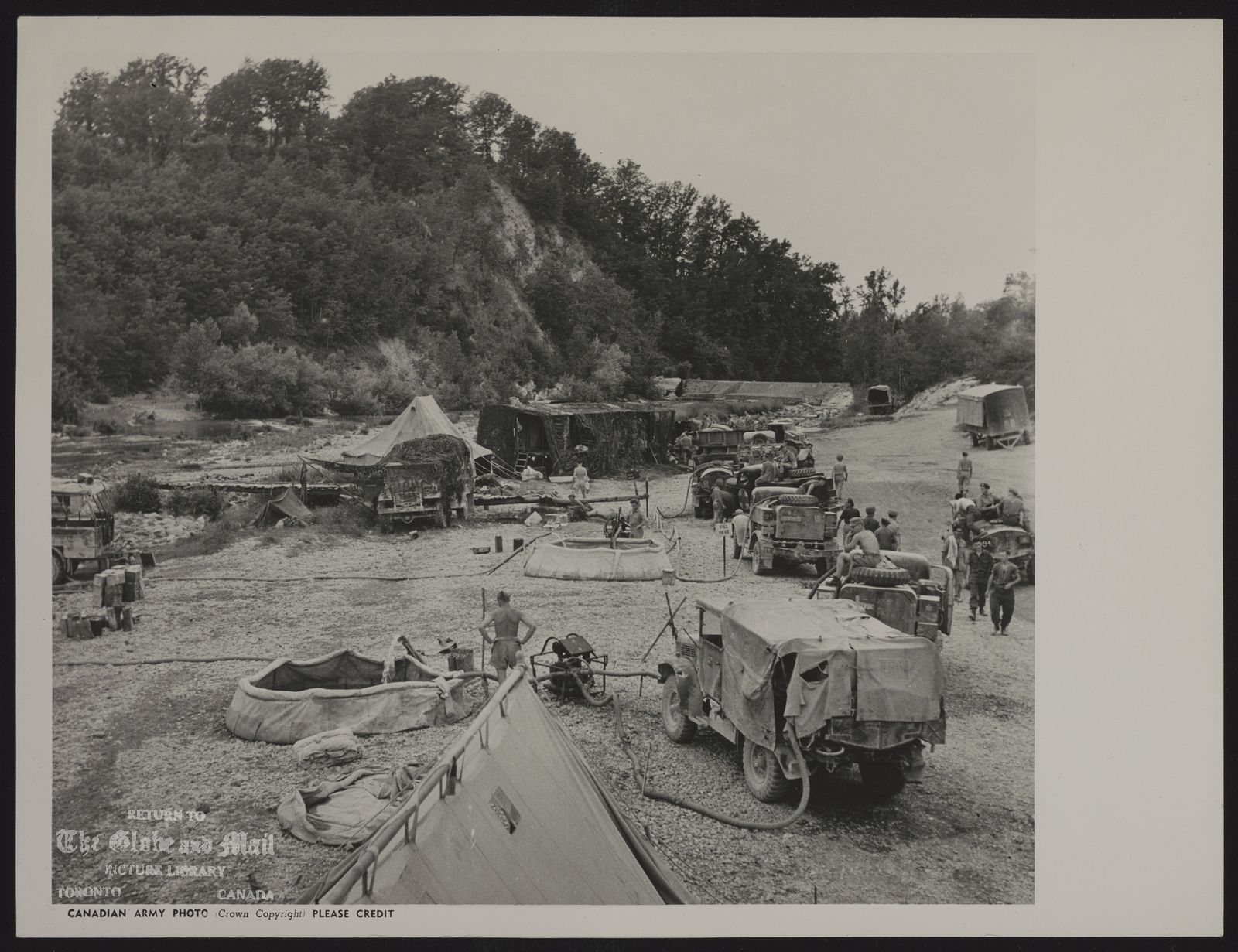 WORLD WAR II FRESH WATER PROBLEM OF CANADIAN'S IN ITALY View of a water purifying unit of the Canadian Army on a Sacco River waterpoint near Pofi in Italy. Pumps are used to bring the water to the purifiers and canvas vats. Water trucks are lined up here for their daily ration for their respective units. (Canadian Army Overseas Photo)
