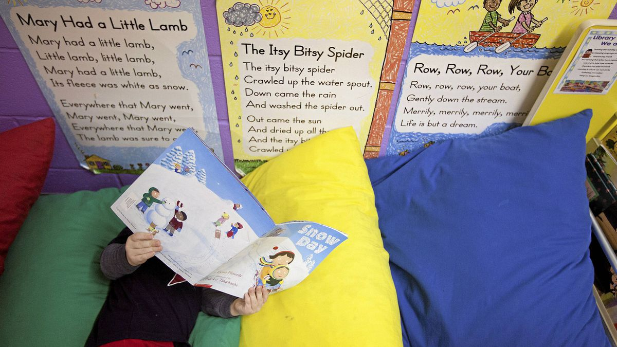 Three-year-old, Brayden Viau reads a book at Acadia Learning Centre in Calgary, Alberta on Dec. 12, 2011.