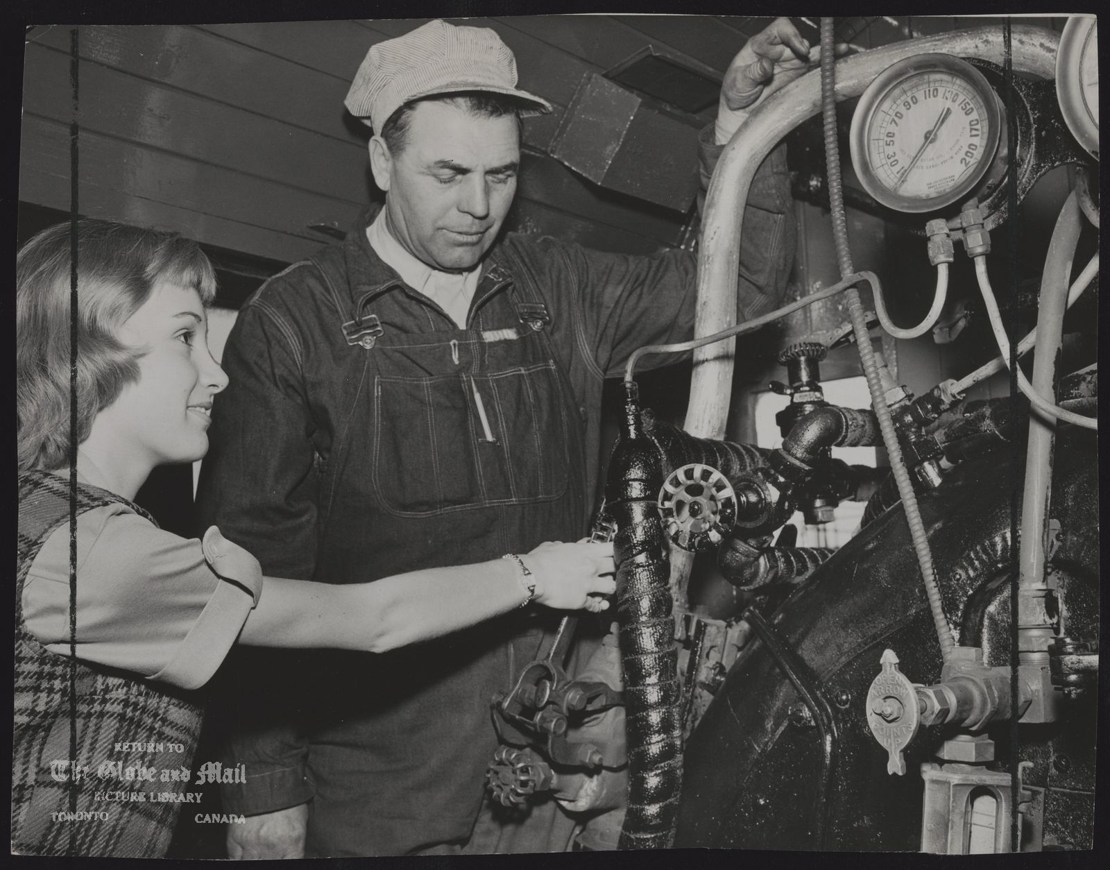 CPR Rolling Stock In the cab, foreman Peter Wilson shows July Miller how the water injector works on Engine 136. [NB: Canadian Pacific 136 is a class A-2-m 4-4-0 steam locomotive built in 1883 by the Rogers Locomotive Works for the Canadian Pacific Railway as No. 140. The locomotive was used for both passenger and freight service for the Canadian Pacific railroad. In 1912 she was renumbered to 115, and the following year she was given her final number and reclassified to A2m. No. 136 was retired from the Canadian Pacific roster in 1960. The engine now remains in operating condition at the South Simcoe Railway in Tottenham, Ontario.]