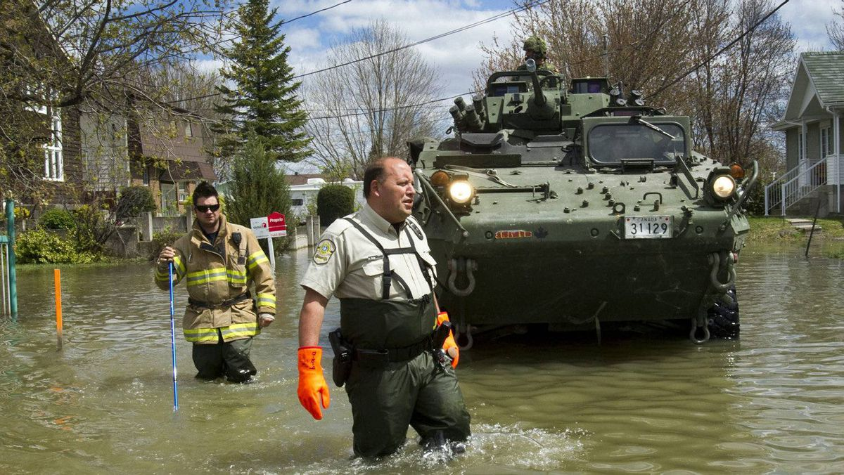 Police and firefighters work with Canadian soldiers wade in a flooded street along the Richelieu River as they check on residents, Monday, May 9, 2011 in Saint-Paul-de-l'�le-aux-Noix, Quebec.