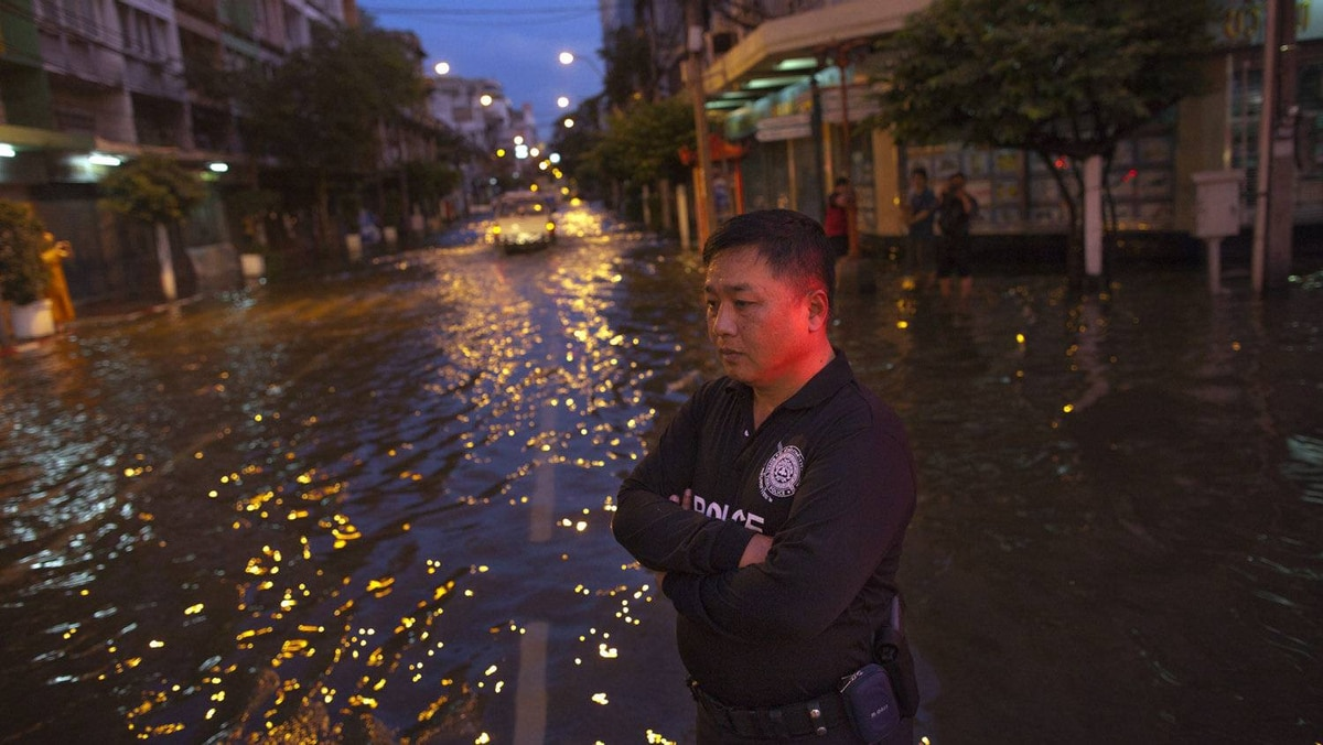 A Thai policeman stands guard helping to direct traffic through the flooded city streets October 26, 2011 in Bangkok. Hundreds of factories are closed as the flood waters began to reach Bangkok. Paula Bronstein/Getty Images