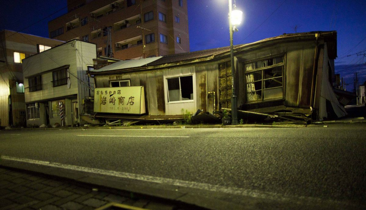 Earthquake damaged buildings sit along an empty street at night in the abandoned town of Namie, inside the 20-kilometer exclusion zone around the Fukushima Daiichi nuclear plant July 10, 2011. A year after the Tsunami, cleanup has begun, but experts say areas inside the nuclear exclusion zone will be difficult to decontaminate.