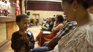 Ethan, 5, shows his mother a photo he took on her camera. They are attending a student concert in which middle son Chad is playing the African drum.