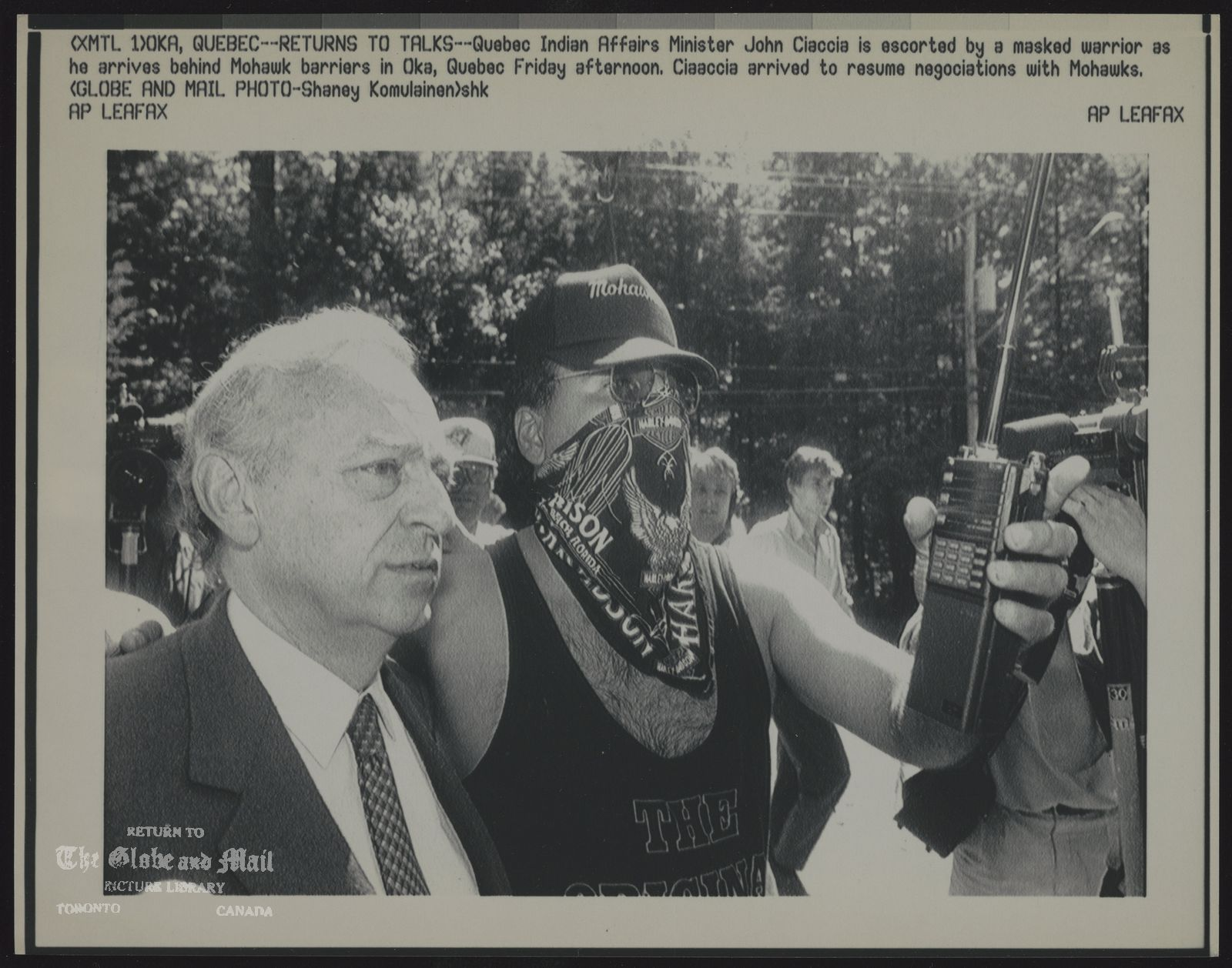 INDIANS CANADA MOHAWKS (XMTL 1) OKA, QUEBEC--RETURNS TO TALKS--Quebec Indian Affairs Minister John Ciaccia is escorted by a masked warrior as he arrives behind Mohawk barriers in Oka, Quebec Friday afternoon. Ciaccia arrived to resume negotiations with Mohawks. (Globe and Mail Photo -- Shaney Komulainen) shk