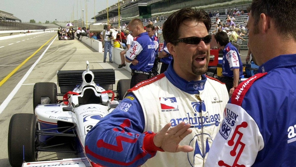 Michael Andretti (left) discusses his car's performance with a crew member in the pits at the Indianapolis Motor Speedway back in 2001.