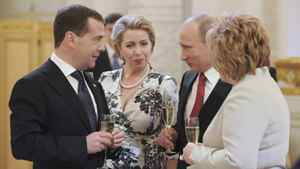 Russia's new President Vladimir Putin (2nd R), his wife Lyudmila, former President Dmitry Medvedev (L) and his wife Svetlana speak during a reception dedicated to the start of Putin's term at the Kremlin in Moscow, May 7, 2012.
