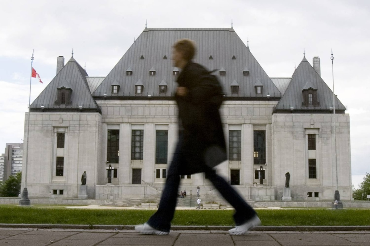 A woman walks past the Supreme Court of Canada in Ottawa.