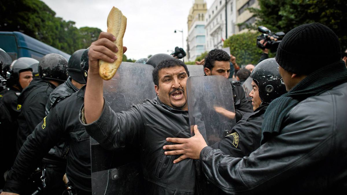 A Tunisian protester holding bread is pushed by riot policemen during a demonstration in Tunis on January 18, 2011.
