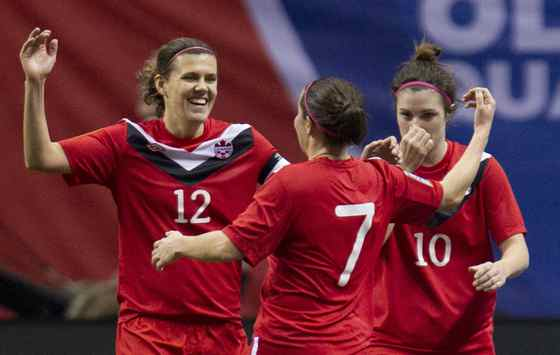 Canada's Christine Sinclair (12) celebrates her goal over Haiti with teammates Rhian Wilkinson (7) and Christina Julien (10) during the first half of CONCACAF Women's Olympic qualifying soccer at B.C. Place in Vancouver, B.C., Thursday, Jan. 19, 2012.