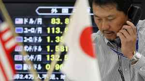 A Japanese foreign currency broker talks on the telephone