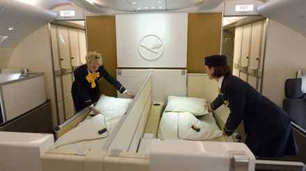 Flight attendants pose as they prepare beds of the First Class in a new Airbus A380 aircraft for Lufthansa.