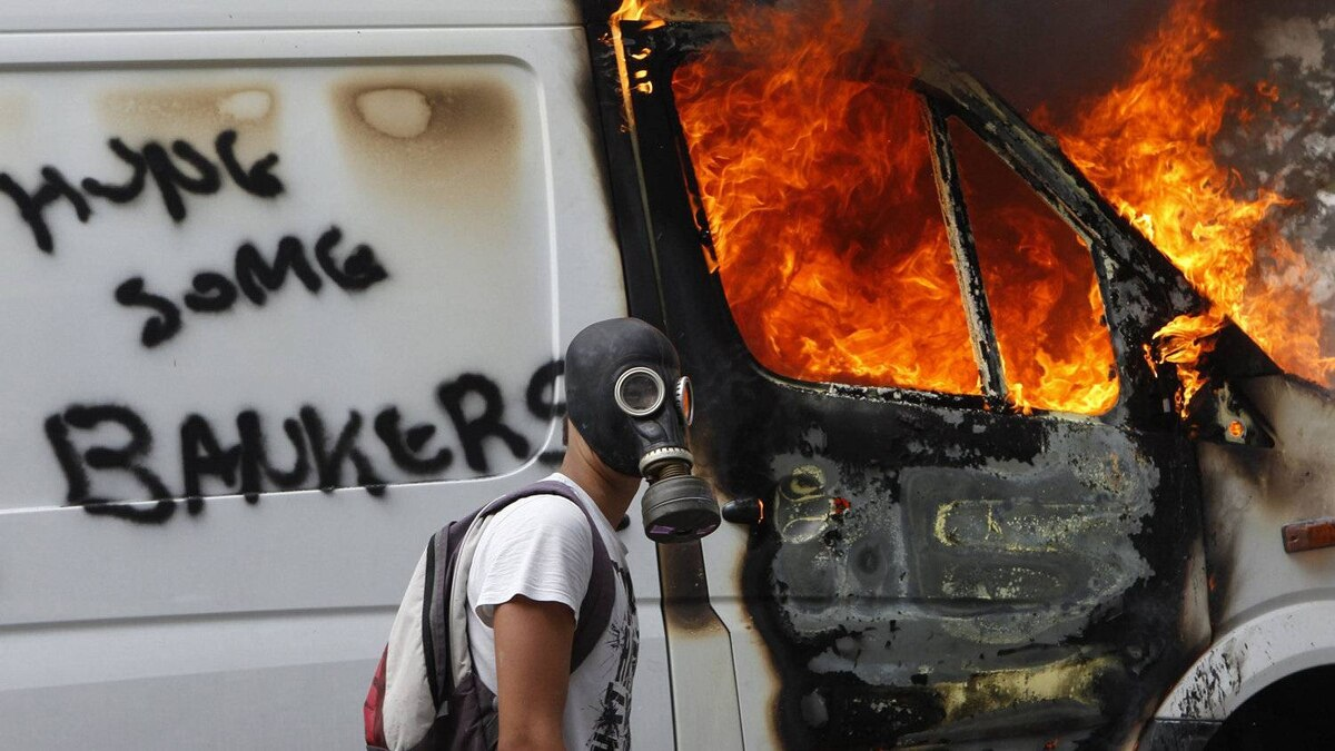 A protester wearing a gas mask walks beside a burning van during violent protests against austerity measures in Athens, June 28, 2011.