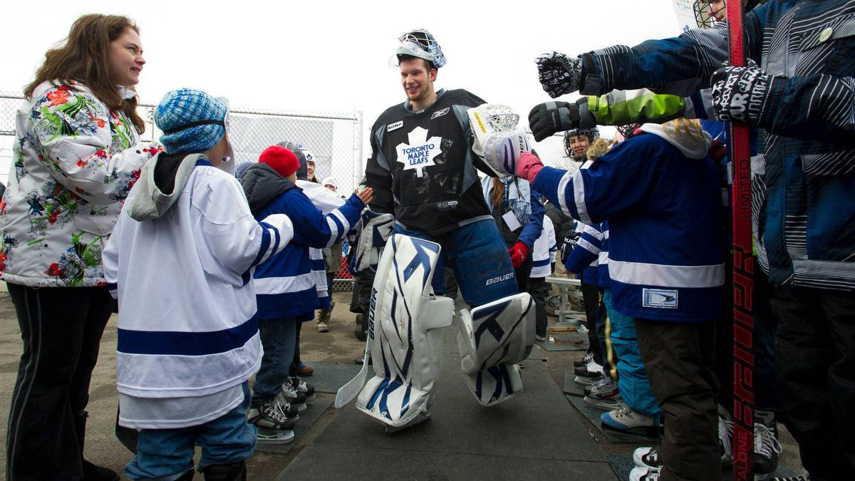 Leafs goalie James Reimer is swarmed by fans as he leaves the ice after the Toronto Maple Leafs held an outdoor practice at Sunnydale Acres Rink in Toronto, Ont.