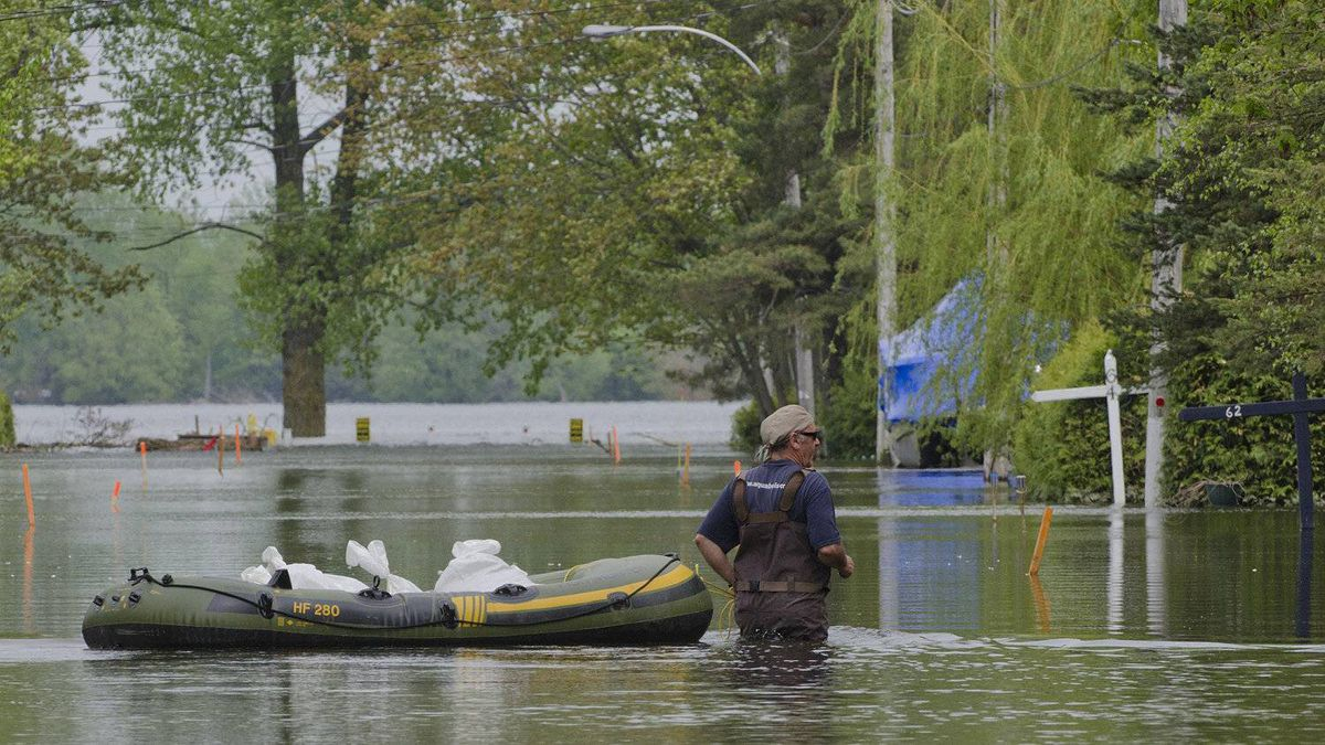 Montrealer Gilles Pilotte drags a inflatable raft filled with sandbags down a flooded street, to a friend's home in Saint-Paul-de-l'�le-aux-Noix, Que.,, May 22, 2011 to help her reinforce her flood barriers against an expected rise in water along the Richelieu River