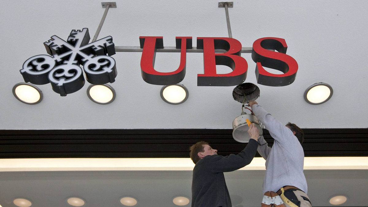 Workers repair a lighting fixture at a UBS bank branch in Zurich.