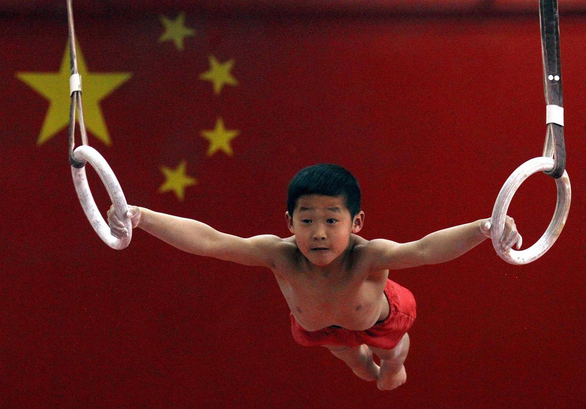 A young gymnast hangs from gymnastic rings in front of a Chinese national flag.