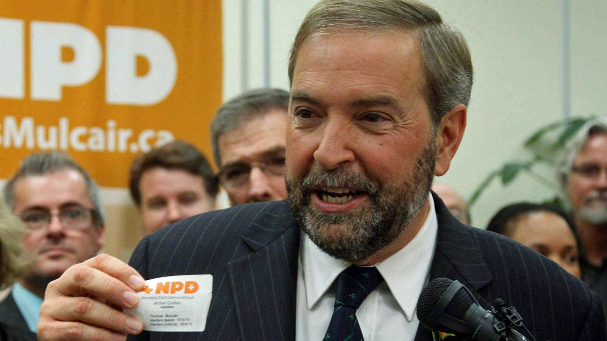 NDP MP Thomas Mulcair holds up his party membership card in his Montreal riding as he announces his bid to succeed Jack Layton as leader on Oct. 13, 2011.l