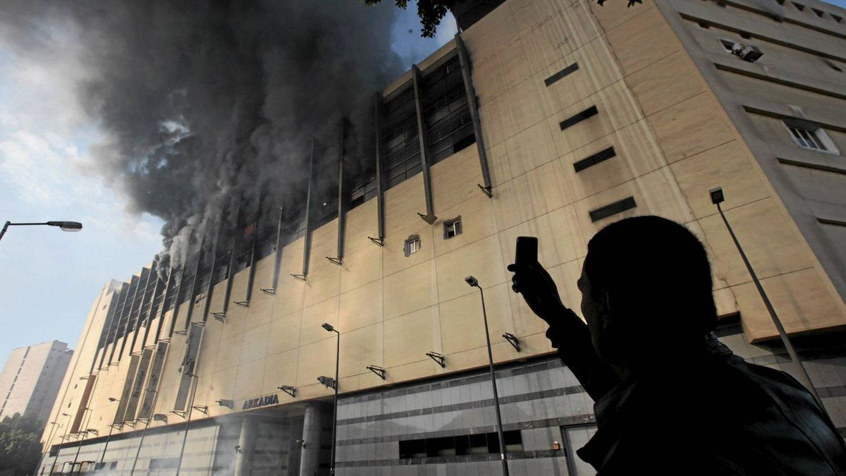 An Egyptian man uses his mobile phone to take a picture of the Arcadia shopping center, that was looted, damaged and set on fire by people in Cairo, Egypt, Sunday Jan. 30, 2011.