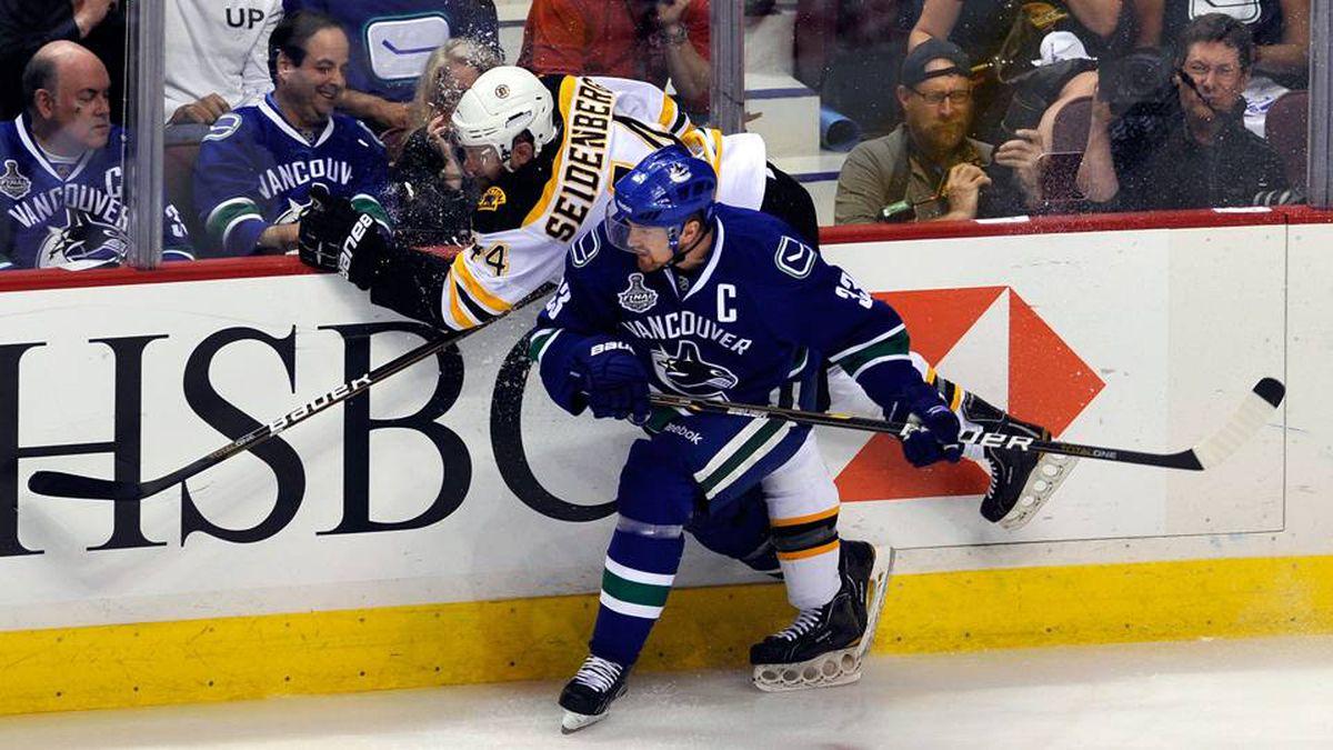 Henrik Sedin of the Vancouver Canucks checks Dennis Seidenberg of the Boston Bruins into the boards.