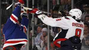 Stickless, New York Rangers defenseman Marc Staal (18) defends himself with his gloves as Washington Capitals left wing Alex Ovechkin (8) checks him in the first period. (AP Photo/Kathy Willens)