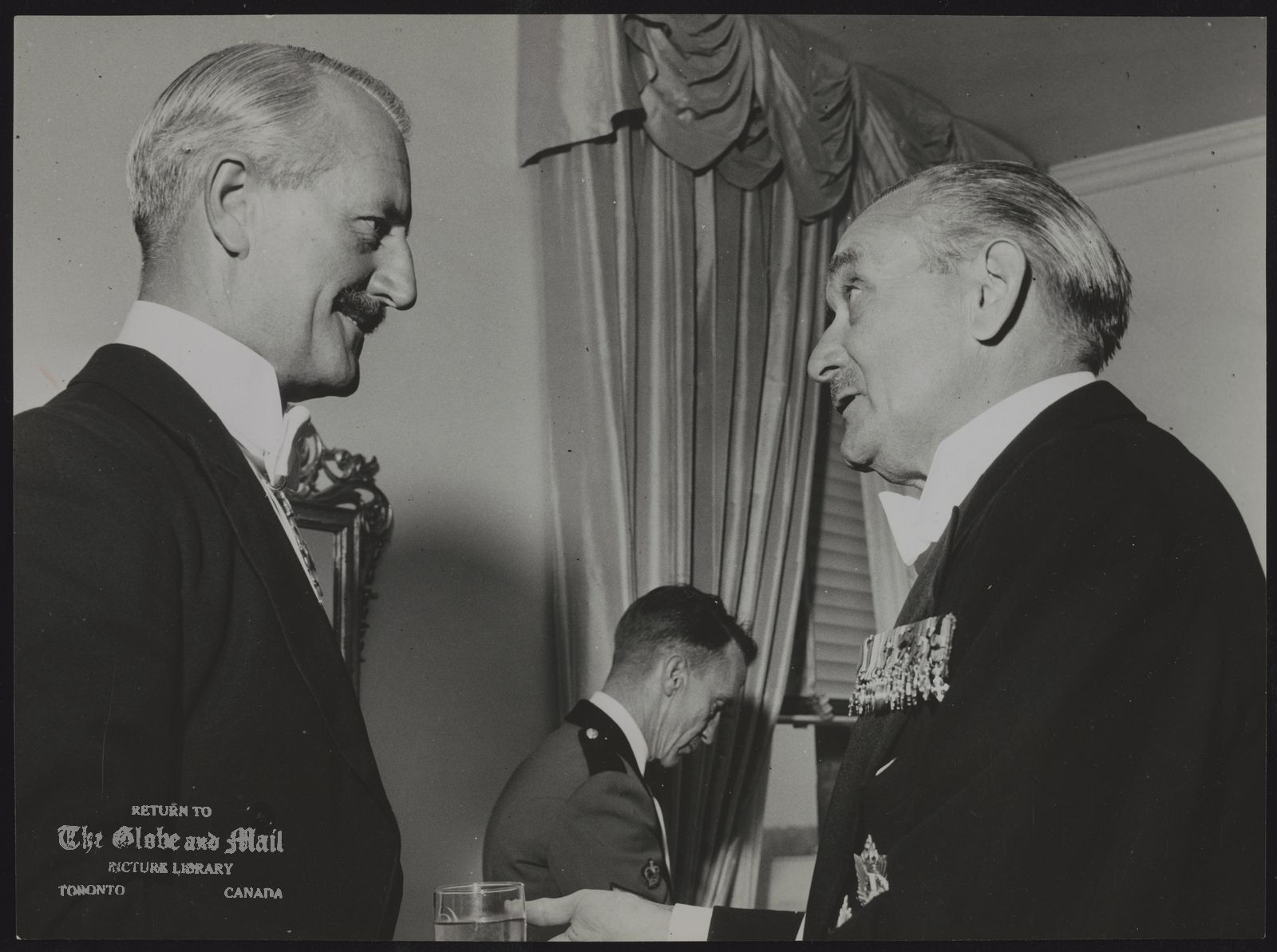 (Maj-Gen) George KITCHING Canada Army Major-General George Kitching (left) and Gen. Charles Foulkes discuss old times at 19th commemoration of D-day landing reunion at the King Edward Hotel in Toronto last night.