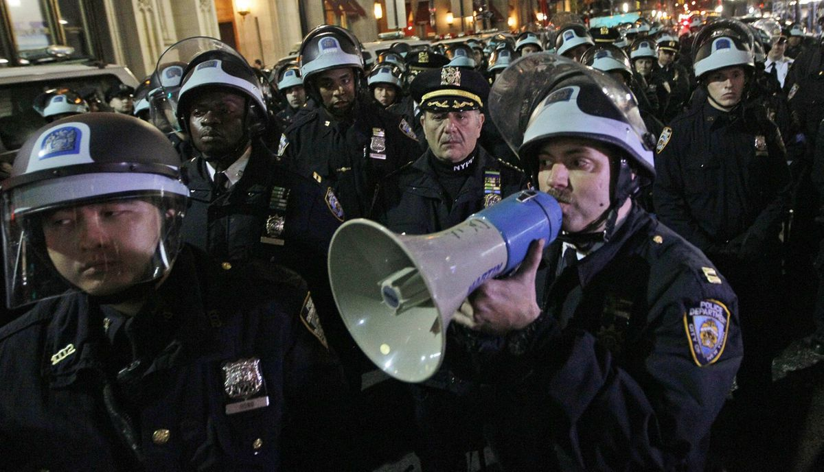 Police officers disperse Occupy Wall Street protesters near the encampment at Zuccotti Park in New York, early Tuesday, Nov. 15, 2011.