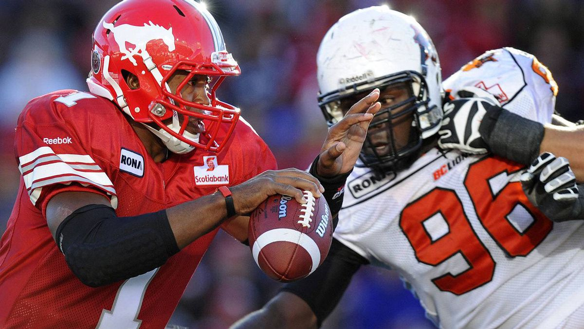 Calgary Stampeders quarterback Henry Burris (L) tries to get away from BC Lions Khalif Mitchell during the first half of their CFL football game in Calgary, Alberta, September 17, 2011. REUTERS/Todd Korol