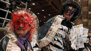 Dressed in costumes adorned with old lottery tickets, a pair of women attend the draw Thursday for Spain's Christmas Lottery 'El Gordo' in Madrid.