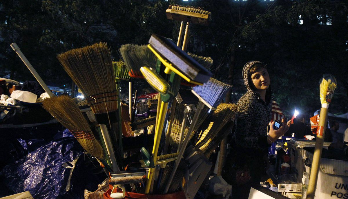 An Occupy Wall Street campaign demonstrator stands near cleaning supplies in Zuccotti Park, near Wall Street in New York October 13, 2011.