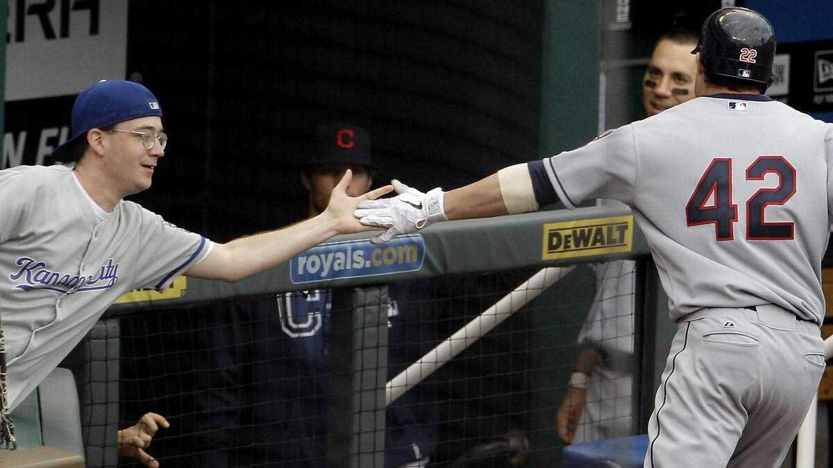 Cleveland Indians' Jason Kipnis is congratulated by a fan as Kipnis comes into the dugout after hitting a solo home run during the eighth inning of a baseball game against the Kansas City Royals on Sunday, April 15, 2012, in Kansas City, Mo. The Indians won 13-7. (AP Photo/Charlie Riedel)