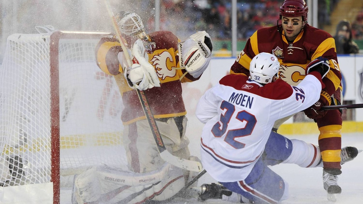 Calgary Flames goalie Miikka Kiprusoff gets sprayed with snow as defenseman Mark Giordano (R) collides with Montreal Canadiens left wing Travis Moen (32) during the second period of their NHL Heritage Classic outdoor hockey game at McMahon Stadium in Calgary, Alberta February 20, 2011. REUTERS/Todd Korol