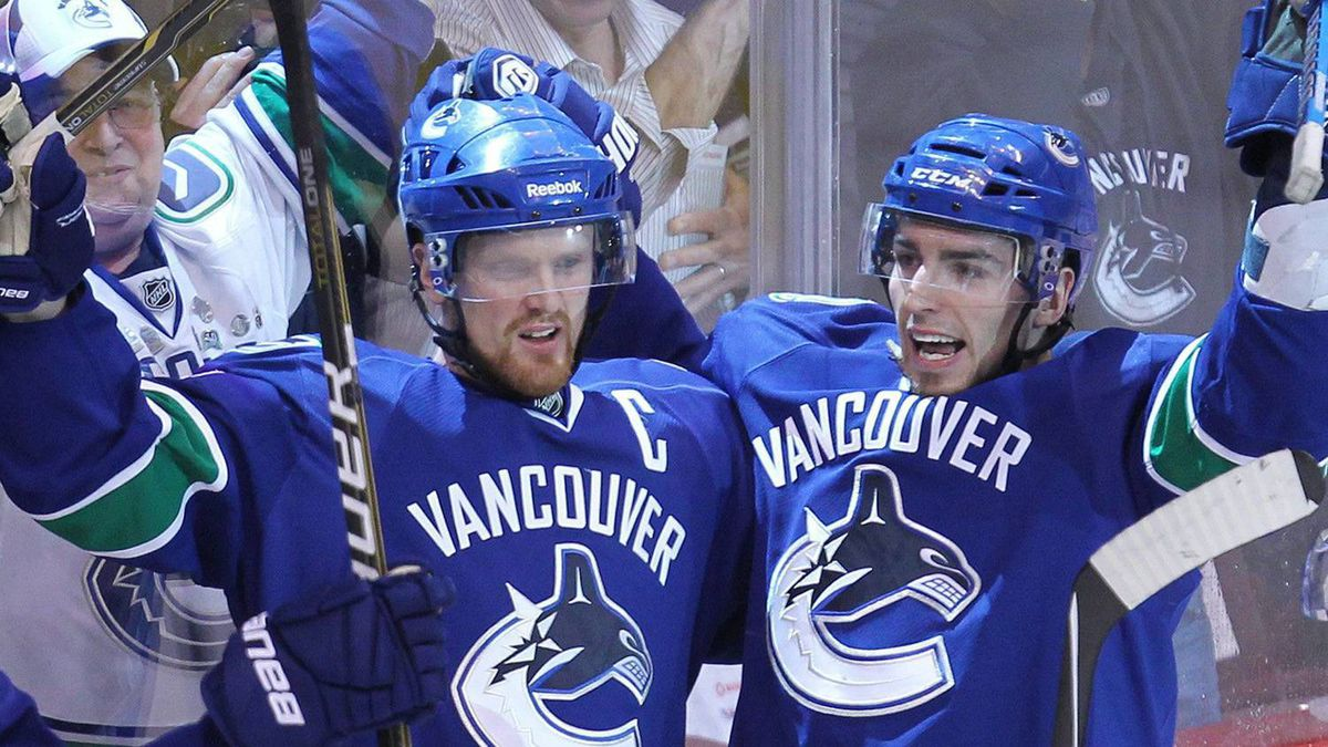 Vancouver Canucks' Alex Burrows, second right, celebrates his goal with teammates Daniel Sedin, of Sweden. THE CANADIAN PRESS/Jonathan Hayward