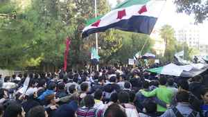 Demonstrators protesting against Syrian President Bashar al-Assad march through the streets of Homs Dec. 6, 2011. Calgary-based Suncor is suspending its operations in the conflict-torn country.