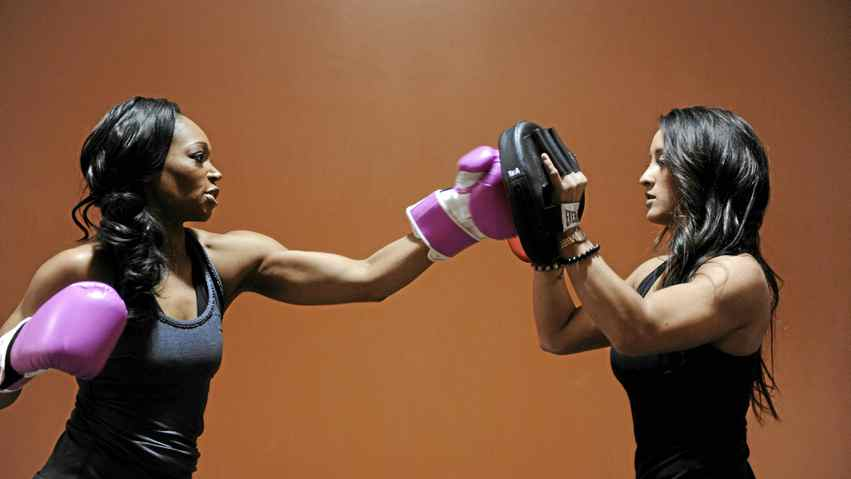 Tracy Moore, left, host of City Tv's Cityline show, works out with personal trainer Stephanie Joanne at an Extreme Fitness.