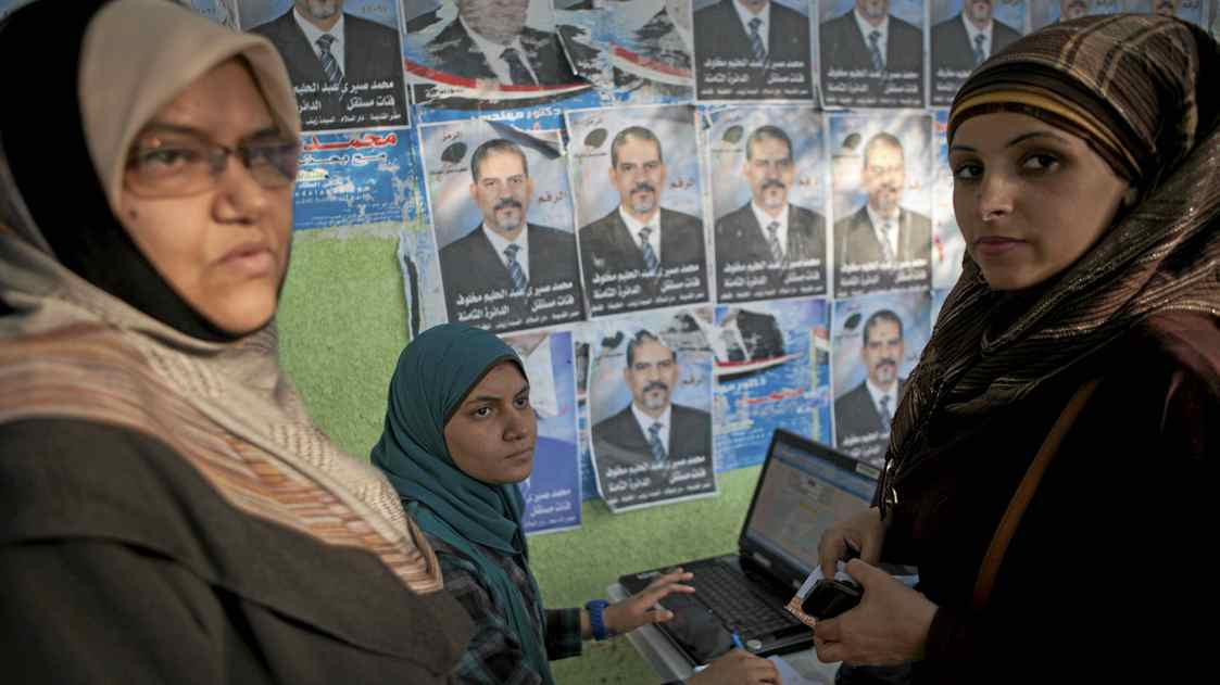 Election volunteers that support the Muslim Brotherhood's Freedom and Justice Party sit at a desk with a computer outside a Cairo polling station on Tuesday.