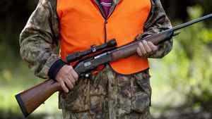 A rifle owner walks through a hunting camp near Ottawa on Sept. 15, 2010.