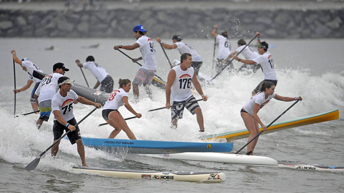 Stand-up paddleboarders catch a wave at the Battle of the Paddle race at Doheny State Beach on Saturday, Sept. 24, 2011, in Dana Point, Calif. Competitors paddle through the surf, run a beach course and paddle around buoys during the race.