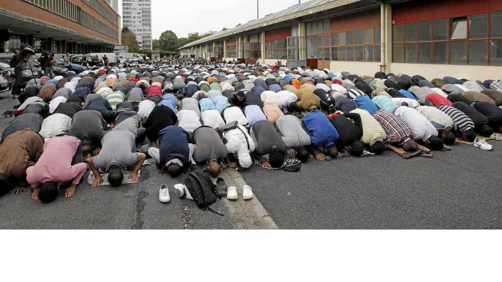 A group of Muslims pray in front of an old barrack in Paris on Sept.16, 2011, as part of Friday prayers. A ban on praying in French streets came into effect today.