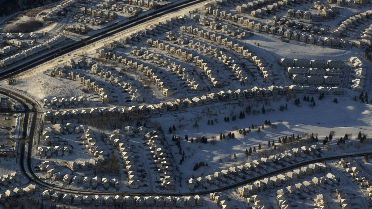 Residential homes are covered in fresh snow as a commercial airliner takes off over Calgary, Alberta December 5, 2011.