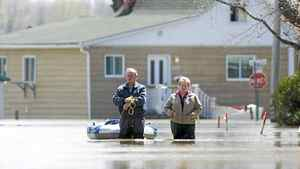 A man and woman make their way along a street immersed by flood waters from the Richilieu River in the town of Saint-Blaise-Sur-Richelieu, Que., Sunday, May 8, 2011.